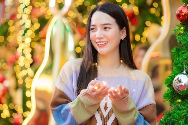 Mulher jovem asiática com cabelo comprido, sorriso adorável segurando uma pequena lâmpada na comemoração do ano novo