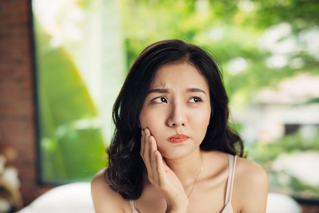 Mulher jovem asiática com dentes doendo em casa.
