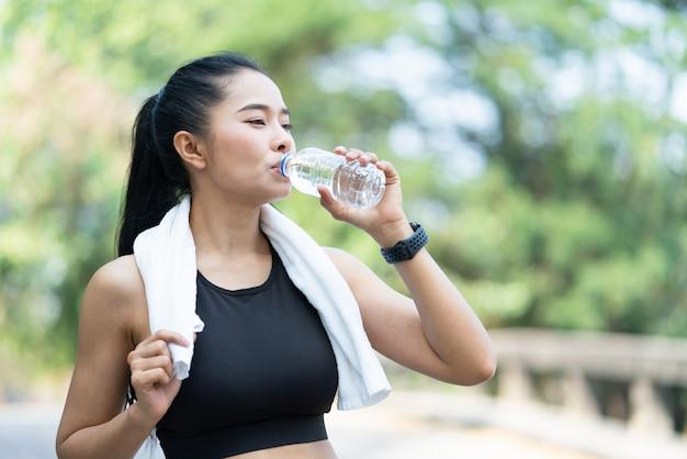 Mulher jovem asiática com esportes com toalha branca bebendo água após exercício físico ao ar livre