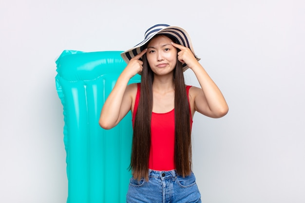 Mulher jovem asiática com um olhar sério e concentrado, fazendo um brainstorming e pensando sobre um problema desafiador