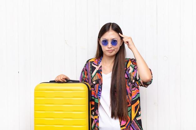 Mulher jovem asiática com um olhar sério e concentrado, pensando em um problema desafiador. conceito de férias