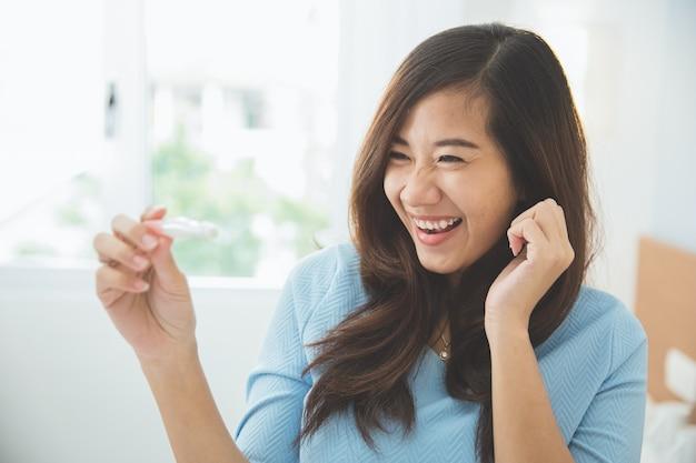 Mulher jovem asiática com um testpack na mão, sorrindo alegremente
