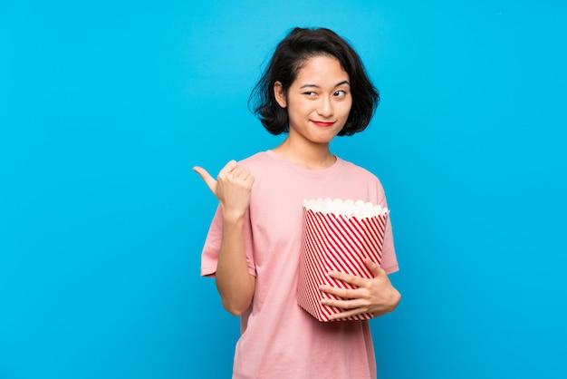 Mulher jovem asiática comendo pipocas apontando para o lado para apresentar um produto