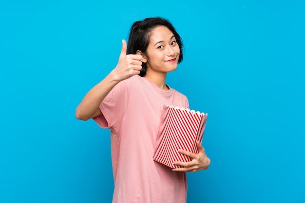 Mulher jovem asiática comendo pipocas com polegares para cima porque algo de bom aconteceu