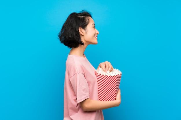 Mulher jovem asiática comendo pipocas