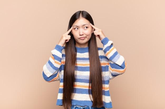 Mulher jovem asiática concentrada e pensando seriamente em uma ideia isolada