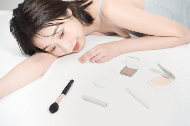 Mulher jovem asiática e itens cosméticos