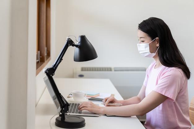 Mulher jovem asiática em camisa rosa, usando máscara protetora branca ou máscara facial e trabalhando em seu computador laptop enquanto está sentado na pequena sala de escritório em casa.