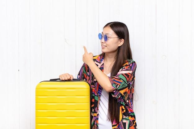 Mulher jovem asiática em pé e apontando para o objeto no espaço da cópia, vista traseira. conceito de férias