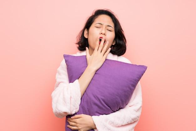 Mulher jovem asiática em pijama e bocejando