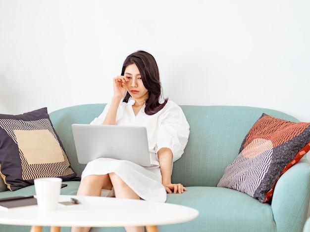 Mulher jovem asiática esfregando os olhos cansados ao usar o laptop.