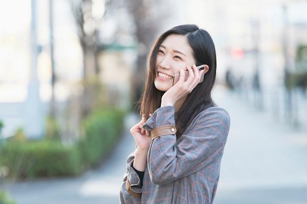 Mulher jovem asiática falando com alguém com smartphone na orelha