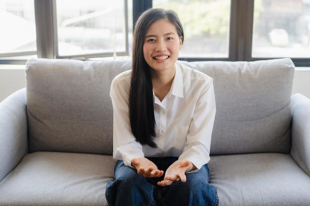 Mulher jovem asiática falando em videoconferência em casa.