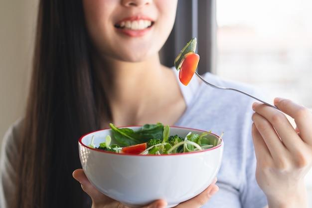Mulher jovem asiática feliz comendo salada verde