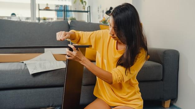 Mulher jovem asiática feliz desempacotando a caixa e lendo as instruções para montar a mobília nova