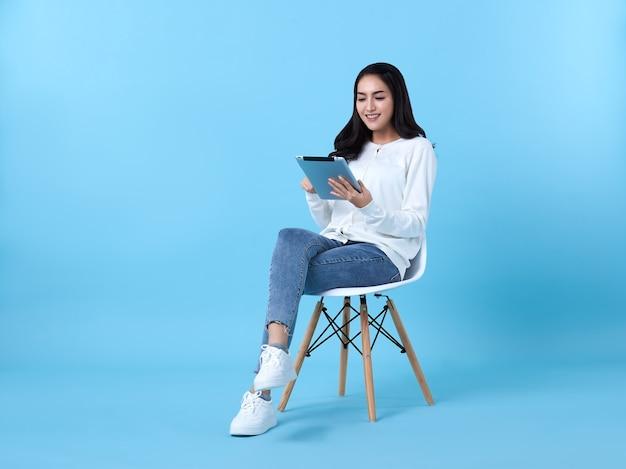 Mulher jovem asiática feliz sorrindo em casaco de lã branco casual com jeans. enquanto ela usa o computador tablet sentado na cadeira branca, isolar sobre fundo azul brilhante.