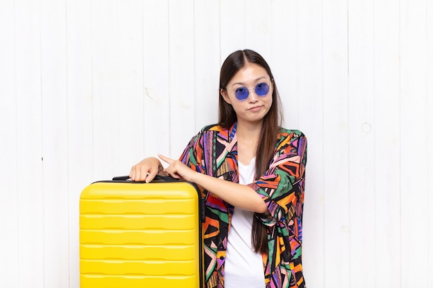 Mulher jovem asiática impaciente e com raiva, apontando para o relógio, pedindo pontualidade, quer ser pontual. conceito de férias