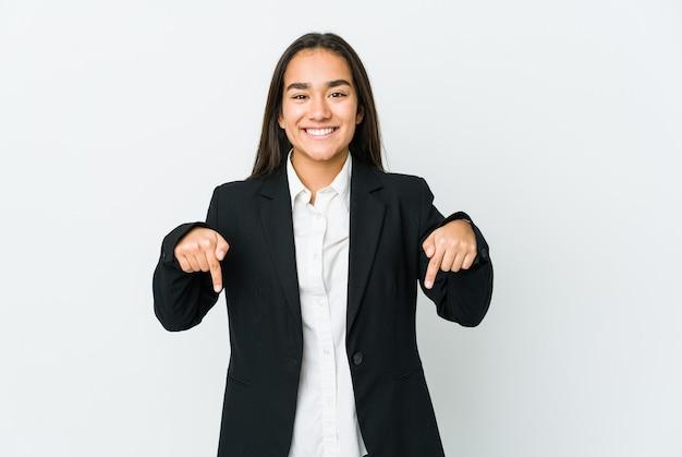 Mulher jovem asiática isolada na parede branca aponta para baixo com os dedos, sentimento positivo.