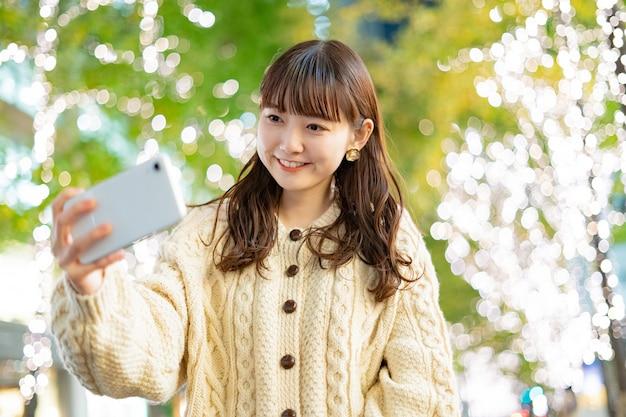 Mulher jovem asiática nas ruas da cidade tomando uma selfie
