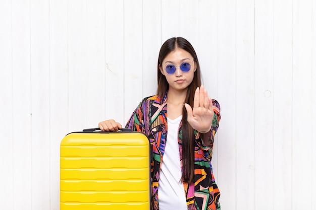 Mulher jovem asiática olhando séria, severa, descontente e com raiva, mostrando a palma da mão aberta, fazendo gesto de parada. conceito de férias