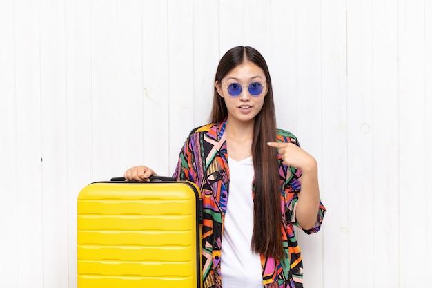 Mulher jovem asiática parecendo chocada e surpresa com a boca bem aberta, apontando para si mesma. conceito de férias