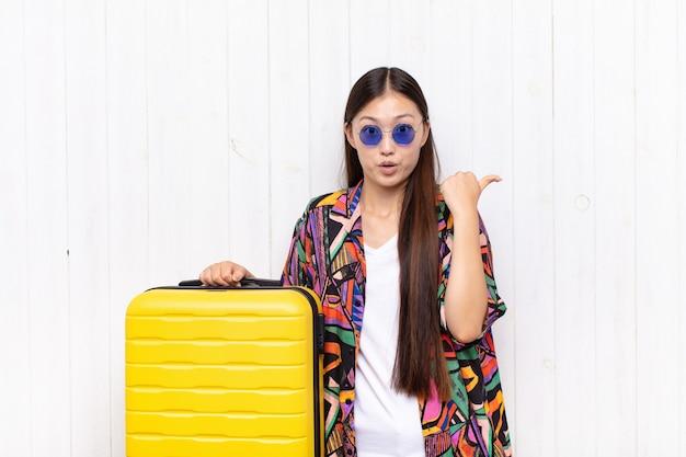 Mulher jovem asiática parecendo espantada com a descrença, apontando para o objeto ao lado e dizendo uau, inacreditável. conceito de férias
