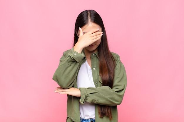 Mulher jovem asiática parecendo estressada, envergonhada ou chateada, com dor de cabeça, cobrindo o rosto com a mão
