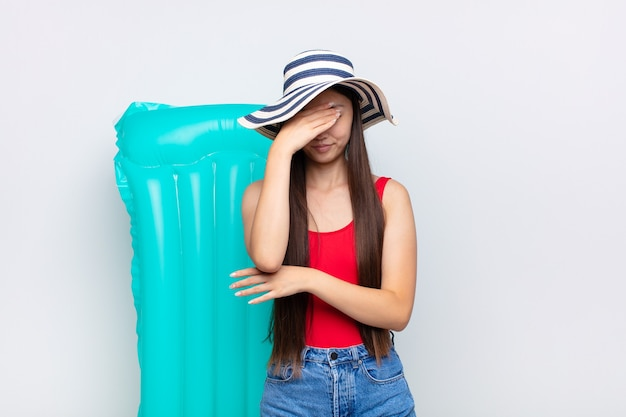 Mulher jovem asiática parecendo estressada, envergonhada ou chateada, com uma dor de cabeça isolada