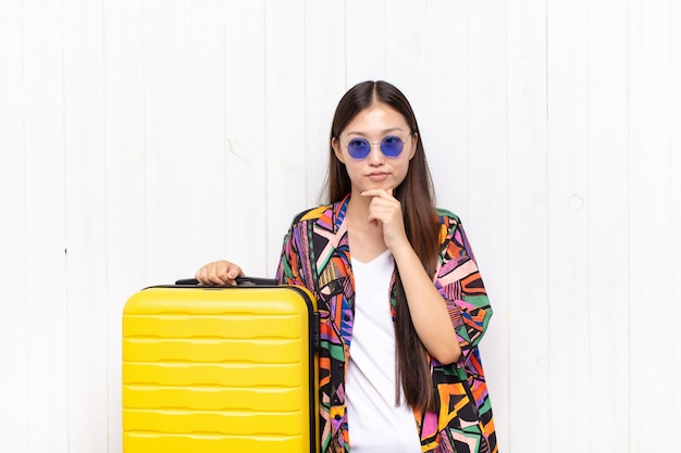 Mulher jovem asiática parecendo séria, confusa, incerta e pensativa, duvidando entre opções ou escolhas. conceito de férias