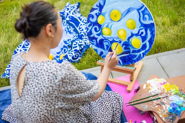 Mulher jovem asiática pintando foto no terraço de casa