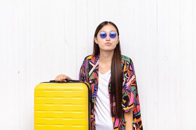 Mulher jovem asiática pressionando os lábios com uma expressão fofa, divertida, feliz e adorável, mandando um beijo. conceito de férias