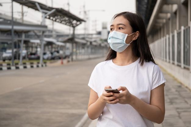 Mulher jovem asiática que mascarou o rosto com máscara protetora de higiene andando por uma longa rua no aeroporto. situação de crise séria no mundo covid19 (2019-ncov).