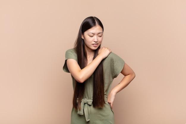 Mulher jovem asiática se sentindo cansada, estressada, ansiosa, frustrada e deprimida, sofrendo de dores nas costas ou no pescoço