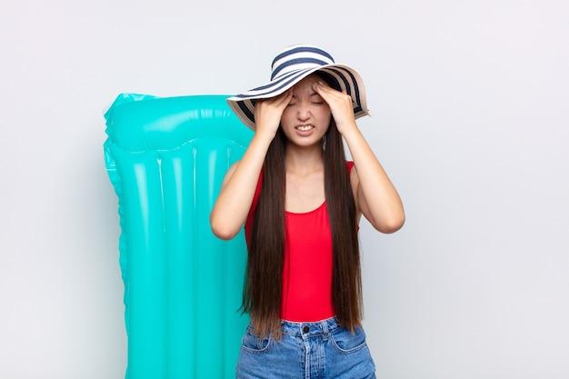 Mulher jovem asiática se sentindo estressada e ansiosa, deprimida e frustrada com uma dor de cabeça, levando as duas mãos à cabeça. conceito de verão