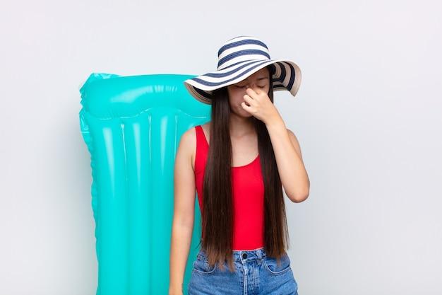 Mulher jovem asiática se sentindo estressada, infeliz e frustrada, tocando a testa e sofrendo de enxaqueca de forte dor de cabeça. conceito de verão