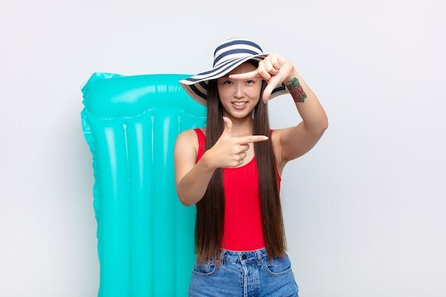 Mulher jovem asiática se sentindo feliz, amigável e positiva, sorrindo e fazendo um retrato ou moldura com as mãos. conceito de verão