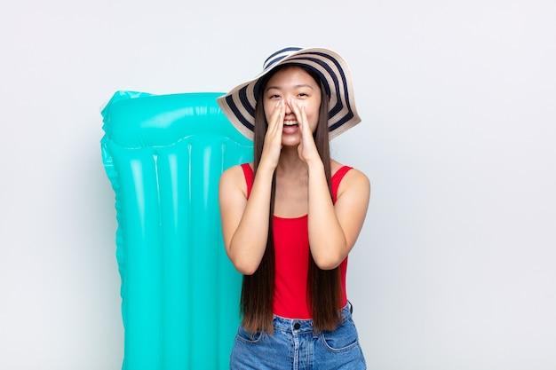 Mulher jovem asiática se sentindo feliz, animada e positiva, dando um grande grito com as mãos perto da boca, gritando. conceito de verão