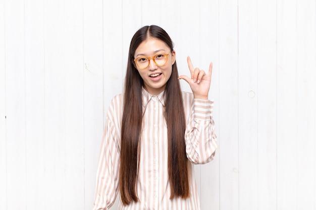 Mulher jovem asiática se sentindo feliz, divertida, confiante, positiva e rebelde, fazendo sinal de rock ou heavy metal com a mão