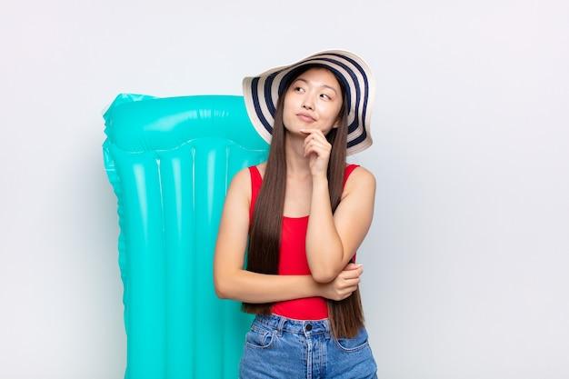 Mulher jovem asiática se sentindo pensativa, pensando ou imaginando ideias, sonhando acordada e olhando para copiar o espaço. conceito de verão