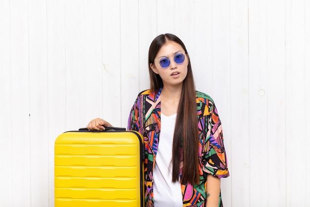 Mulher jovem asiática se sentindo perplexa e confusa, com uma expressão muda e atordoada olhando para algo inesperado. conceito de férias
