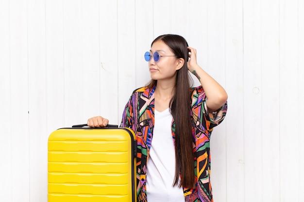 Mulher jovem asiática se sentindo sem noção e confusa, pensando em uma solução, com a mão no quadril e a outra na cabeça, vista traseira. conceito de férias