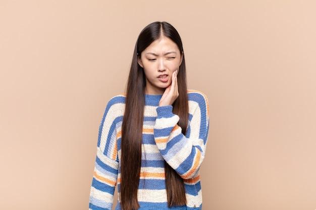Mulher jovem asiática segurando a bochecha e sofrendo de uma dor de dente dolorosa, sentindo-se doente, infeliz e infeliz, procurando um dentista
