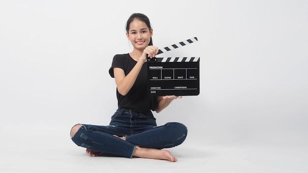 Mulher jovem asiática segurando claquete preta ou ardósia de filme ou ripa e sentar no chão. ele usa na produção de vídeo, filme, filme, indústria do cinema em fundo branco.