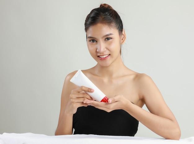 Mulher jovem asiática segurando o tubo de creme hidratante