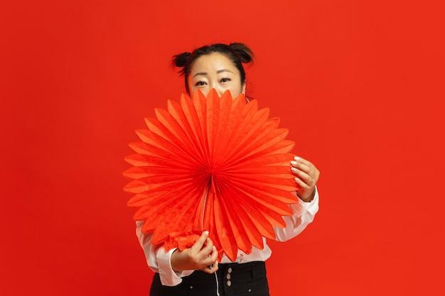 . mulher jovem asiática segurando uma lanterna grande na parede vermelha em roupas tradicionais. sorridente, fofo, parece feliz. celebração, emoções humanas, feriados. copyspace para anúncio.