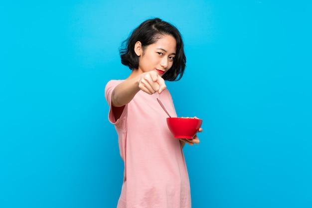 Mulher jovem asiática segurando uma tigela de cereais aponta o dedo para você com uma expressão confiante