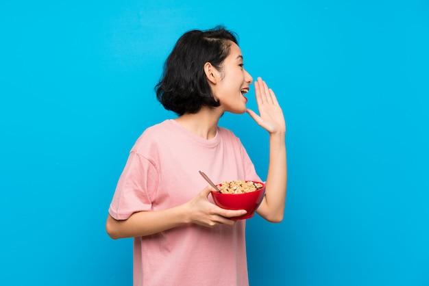 Mulher jovem asiática segurando uma tigela de cereais, gritando com a boca aberta
