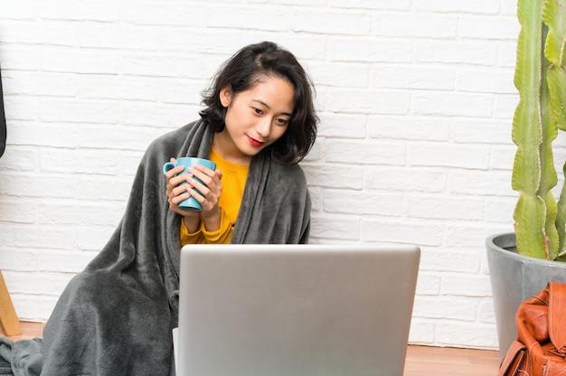 Mulher jovem asiática sentada no chão segurando uma xícara de café