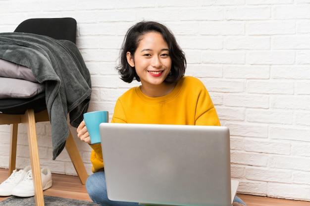 Mulher jovem asiática sentada no chão, segurando uma xícara de café