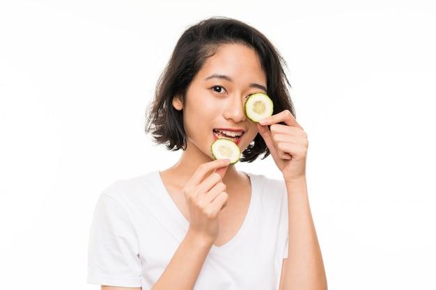 Mulher jovem asiática sobre parede isolada segurando fatias de pepino